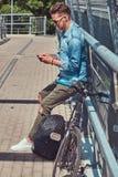 Pantaloni a vita bassa bei con taglio di capelli alla moda in occhiali da sole che riposano dopo la guida su una bicicletta, face Fotografia Stock