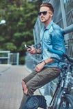 Pantaloni a vita bassa bei con taglio di capelli alla moda in occhiali da sole che riposano dopo la guida su una bicicletta, tenu Immagini Stock