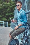 Pantaloni a vita bassa bei con taglio di capelli alla moda in occhiali da sole che riposano dopo la guida su una bicicletta, tenu Immagine Stock