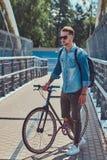 Pantaloni a vita bassa bei con un taglio di capelli alla moda in occhiali da sole che camminano con la bicicletta all'aperto Fotografie Stock Libere da Diritti
