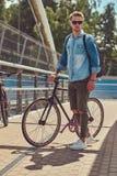 Pantaloni a vita bassa bei con un taglio di capelli alla moda in occhiali da sole che camminano con la bicicletta all'aperto Fotografia Stock Libera da Diritti