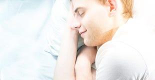 Pantaloni a vita bassa bei del tipo, non rasato, addormentati nel suo letto bianco, vicino Immagine Stock