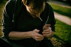 Pantaloni a vita bassa che accendono una sigaretta - godendo del fumo fuori fotografie stock