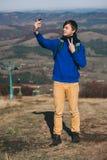 Pantaloni a vita bassa che prendono foto dallo Smart Phone sul picco della montagna Fotografia Stock
