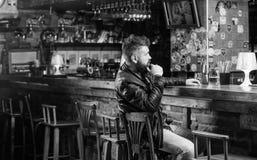 Pantaloni a vita bassa che si rilassano alla barra con birra Uomo con la barba spendere svago nella barra scura L'uomo barbuto de fotografia stock