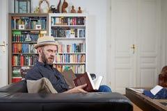 Pantaloni a vita bassa con il cappello che leggono un libro a casa Fotografia Stock Libera da Diritti