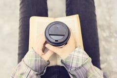 Pantaloni a vita bassa con un libro e una tazza da caffè all'aperto Immagini Stock