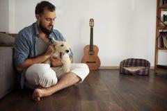 Pantaloni a vita bassa dell'uomo con il cane bianco Fotografie Stock
