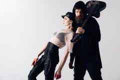 Pantaloni a vita bassa e donna alla moda insieme alla chitarra elettrica Oscilli le coppie della ragazza sexy e dell'uomo barbuto fotografia stock libera da diritti