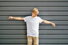 Pantaloni a vita bassa esili con due armi alzate vicino alla parete grigia in una b fotografia stock libera da diritti