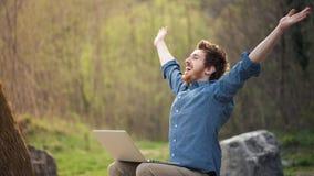 Pantaloni a vita bassa felici con il computer portatile nella foresta Fotografia Stock