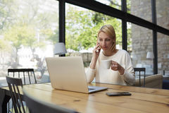 Pantaloni a vita bassa femminili che hanno conversazione dello smartphone che lavora alla tavola di legno Immagini Stock