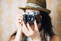 Pantaloni a vita bassa femminili che prendono foto con la retro macchina fotografica Fotografia Stock