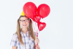 Pantaloni a vita bassa Geeky che sorridono alla macchina fotografica e che tengono i palloni rossi Immagine Stock