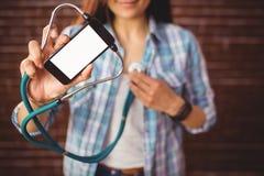 Pantaloni a vita bassa graziosi che per mezzo del suo smartphone per diagnosticare Fotografia Stock Libera da Diritti