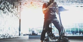 Pantaloni a vita bassa maschii tatuati barbuti che utilizzano telefono cellulare dopo la guida in motorino elettrico nella città  fotografia stock libera da diritti