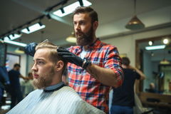Pantaloni a vita bassa nel negozio di barbiere immagine stock