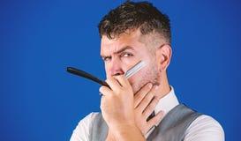 Pantaloni a vita bassa non rasati del barbiere con il rasoio diritto del pericolo tagliente Salone del parrucchiere del parrucchi fotografia stock