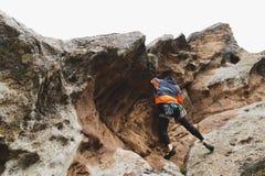 Pantaloni a vita bassa - scalatore all'età dello scalare una bella roccia senza assicurazione e casco Immagine Stock
