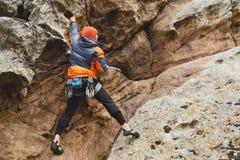 Pantaloni a vita bassa - scalatore all'età dello scalare una bella roccia senza assicurazione e casco Fotografie Stock