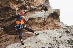 Pantaloni a vita bassa - scalatore all'età dello scalare una bella roccia senza assicurazione e casco Immagini Stock Libere da Diritti