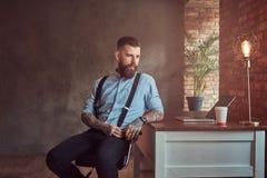 Pantaloni a vita bassa tatuati bei in camicia e bretelle che si siedono allo scrittorio con un computer, guardante fuori la fines Fotografia Stock