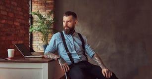 Pantaloni a vita bassa tatuati bei in camicia e bretelle che si siedono allo scrittorio con un computer, guardante fuori la fines Immagini Stock Libere da Diritti