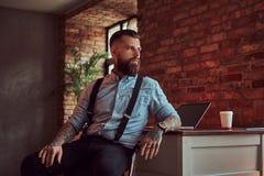 Pantaloni a vita bassa tatuati bei in camicia e bretelle che si siedono allo scrittorio con un computer, guardante fuori la fines Fotografia Stock Libera da Diritti