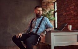 Pantaloni a vita bassa tatuati bei in camicia e bretelle che si siedono allo scrittorio con un computer, guardante fuori la fines Immagine Stock Libera da Diritti