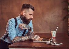 Pantaloni a vita bassa tatuati bei in camicia e bretelle che si siedono allo scrittorio, lavorante ad un computer portatile, in u Fotografia Stock Libera da Diritti
