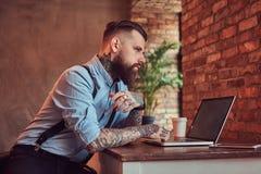 Pantaloni a vita bassa tatuati bei in camicia e bretelle che si siedono allo scrittorio, lavorante ad un computer portatile, in u Immagini Stock