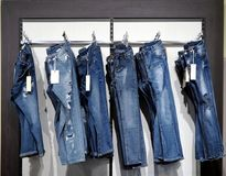 Pantalons de denim accrochant sur un cintre dans le mur d'un magasin images libres de droits