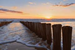 Pantanos de madera que corren en el mar con puesta del sol fotografía de archivo