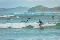 10/06/2017 Pantau Mawun, Lombok, Indonesien Den unga kvinnan lär att surfa Arkivfoto