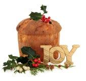 Pantettone Christmas Cake. Panetone christmas cake with joy glitter sign, holly, mistletoe, ivy and cedar cypress leaf sprigs over white background Royalty Free Stock Photo