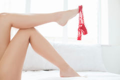Panties on foot. Close-up on beautiful women's leg with panties Royalty Free Stock Photo