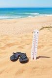 Pantoffel auf dem Strand neben dem Thermometer und dem Meer. Stockbilder