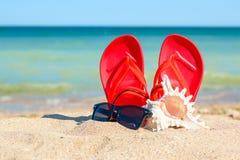 Pantoffel, Sonnenbrille und Oberteil im Sand Stockbilder