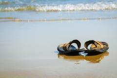 Pantoffels op oceaanstrand Stock Foto