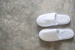 Pantofola bianca del panno sul pavimento di calcestruzzo a casa Fotografia Stock Libera da Diritti