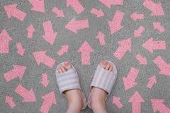 Pantofola calda a quadretti Scarpe rosa d'uso stanti della femmina con la direzione rosa delle frecce sui precedenti del cemento Fotografia Stock Libera da Diritti
