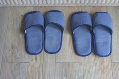 Pantofole comode blu di vista superiore due paia sul pavimento di legno nella camera da letto fotografie stock