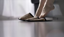 Pantofole d'uso della donna che si alzano dal letto immagini stock libere da diritti