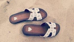 Pantofole di estate sulla sabbia della spiaggia fotografia stock