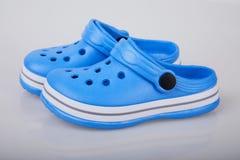 Pantofole di gomma blu, isolate su fondo bianco fotografia stock