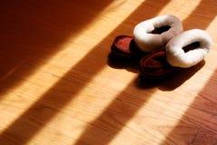 Pantofole di inverno del bambino sul pavimento di legno duro Fotografia Stock