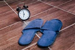 Pantofole e sveglia blu bedtime La vista dalla parte superiore fotografie stock libere da diritti