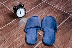 Pantofole e sveglia blu bedtime La vista dalla parte superiore fotografia stock libera da diritti
