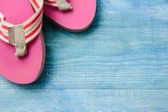 Pantofole rosa su un fondo di legno blu, sul fondo di estate e Fotografie Stock Libere da Diritti