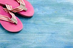 Pantofole rosa su un fondo di legno blu, sul fondo di estate e Fotografia Stock